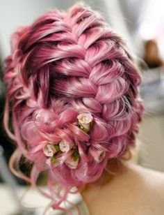 This dreamy hairstyle has everything we love: flowers, braids, and pink hair.
