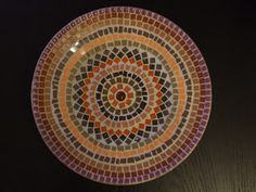 Mosaic bowl with glass, tile and more in brown, orange and purple.
