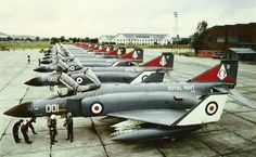 """892 Naval Air Squadron at RAF Leuchars, 1976, ready to embark to HMS Ark Royal. 892 Squadron was the front line squadron and was based at RNAS Yeovilton, Somerset. 892 Squadron's badge was prominent on the fin in red, white and black; the black letter """"Omega"""" was chosen for the marking as it is the last letter of the Greek alphabet, and at the time it was thought that 892 would be the last fixed-wing Naval Squadron."""