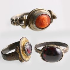 Jewelry Auction - NO RESERVE ITEM - Nov 30th 2016 - First, a bronze ring with thin band joined to an oval bezel with polished garnet cabochon. - Second, a metal ring with wide band, joined to a flat oval bezel with heightened center set with a garnet cabochon. - Third, a silver gilt ring with rounded band, flat on the interior, and decorated with Baroque ornaments on the shoulders. This and more important jewelry for sale on CuratorsEye.com