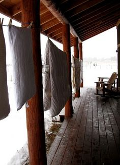 hanging on the porch of a log cabin in winter ~ imagine going to sleep under the comforter smelling like winter ~ cozy ~