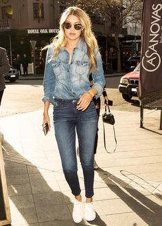 Gigi Hadid in a denim shirt, dark denim skinny jeans, white sneakers, and sunglasses