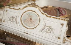 1901, New York, serial number 99,999, the paneled case raised on fluted tapering circular legs joined by shaped stretchers, grey-painted with gilt-highlighted carved ornament, the exterior of lid polychrome-painted with a border of foliate scrolls, urns and cartouches enclosing profile portraits of various composers painted en grisaille, the interior of lid painted with a scene of a shepherd instructing a maiden in playing a flute, observed by more maidens and a young man concealed by a…