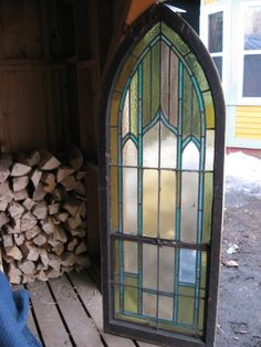 Antique gothic arched stained glass church window. Pretty blues and greens.