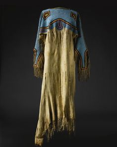 A LAKOTA BEADED AND FRINGED HIDE DRESS    composed of finely tanned hide, glass beads, and sinew.  Length 61 in.