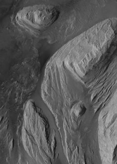 Outcrops in East Candor Chasma - This Mars Global Surveyor (MGS) Mars Orbiter Camera (MOC) image shows light-toned, wind-eroded, sedimentary rock outcrops in eastern Candor Chasma, part of the Valles Marineris trough system.  Credit: NASA/JPL/Malin Space Science Systems | via redOrbit.com
