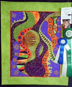 """""""Convergence"""" by Darlynn Evans was inspired by the Australian quilter Gloria Loughman. Darlynn created and embellished each piece individually and then put it all together. The detail and workmanship are exquisite. She used teeny tiny satin stitch in places and there are all sorts of lovely details that you cannot see from this photo."""