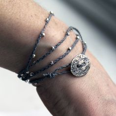 Grey waxed Irish linen cord is braided and embellished with a galaxy of tiny round sterling silver beads. Closes with a sterling silver artisan button.