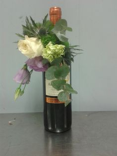 a corsage on a bottle of wine. With Lisianthus, white rose, Green thick, Hypericum, galax and Eucalypthus