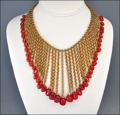 Incredible runway Miriam Haskell vintage 1920s fringe bib Art Deco necklace! Carnelian red orange art glass beads dangle in a chevron from double chains of gold gilt brass. Gilt brass petal caps top each bead. The chains are suspended from a single double loop chain ending in a simple spring ring clasp. The necklace has been attributed to Miriam Haskell and is an absolutely breathtaking piece!    Measurements: 15 with the longest point of the chevron V in the front measuring 4  Circa…