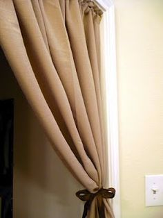 Tension rods are great!  Here in a doorway with a tied back curtain for a bit of style and drama (and privacy).  Leaves no holes and looks great!