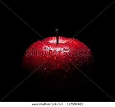 fresh red apple with droplets of water against black background with space for…