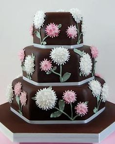 Contempory, three tier chocolate hexagon wedding cake, decorated with unusual white and pink buttercream flowers with green leaves and stems. From www.maisiefantaisie.co.uk