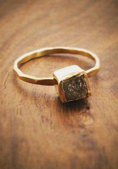 raw diamond chunk ring-18 karat gold    A unique and beautiful raw diamond chunk is encased in a hand made, high wall bezel, floating on an 18 karat hammered gold ring. This ring is extraordinarily unique. Designed so that it can be stacked with our other diamond rings, this ring is also a stunner on its own. The chunk measures about 4 mm square and sits about 4 mm above the finger. Shape and color of each stone varies.