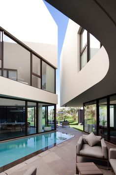 """""""Mop house"""". A single family residence in kuwait. two loosely interlocked volumes form an open air courtyard, creating a clear separation between either half of the house. a private and public entrance lead to the outdoor swimming pool and ground level living spaces which border a glass wall for visual connection across the courtyard."""