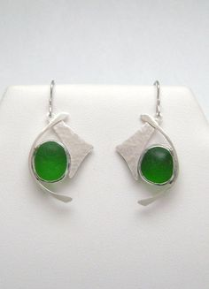 The green sea glass are genuine. They were found and supplied by....  https://www.etsy.com/shop/mamzelleseaglass and are no back bezel set. The