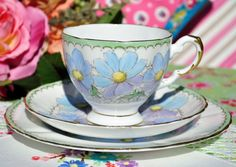 Vintage Tuscan fine bone china tea cup, saucer and tea plate. c.1936+ Hand painted blue and lilac flowers with yellow centres on a crazy paving background and with a pale green border. The tea cup is 8cm wide at the rim x 7cm tall. The saucer is 14cm diameter and the tea plate is 17.5cm. Gold gilding to the scallop shaped rims and lovely gilded detail on the teacup handles. Tuscan fine bone china. Made by R. H. and S. L. Plant, Tuscan Works, Longton, Staffordshire Potteries, England. Date…