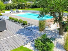 La piscine paysagée par l'esprit piscine - 9,5 x 4 m Revêtement blanc Escalier droit sur la largeur Margelles et plage en ipé