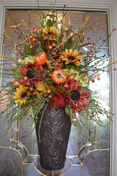 This arrangement is made in a metal container and can be hung on a door or wall. It is full of sunflowers, fall berries and pumpkins and is perfect for the upcoming fall months.. measures 18 x30.