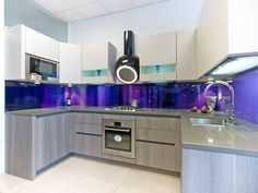 Abstract chromatic image on glass splashback in contemporary kitchen.