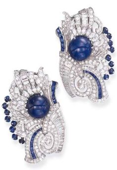 A PAIR OF ART DECO DIAMOND AND SAPPHIRE CLIP BROOCHES. Each designed as an openwork old European and single-cut diamond scrolling plaque of foliate motif, centring upon a cabochon sapphire, accented by marquise-cut diamonds, further enhanced by baguette-cut sapphire and diamond detail and sapphire bead trim, mounted in platinum, circa 1930. #ArtDeco #ClipBrooch