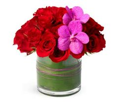 V19 Violet Embrace A low compact mount of red roses is accented with a bright pink Vanda orchid and matching wire in a Ti Leaf wrapped glass cylinder vase for a sweet and simple arrangement for your love. #Valentine's Day