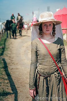 Medieval girl with apron on the straw hat as protection against the sun