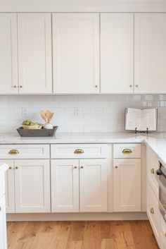 White shaker cabinetry with brass cups and knobs - by Rafterhouse ...
