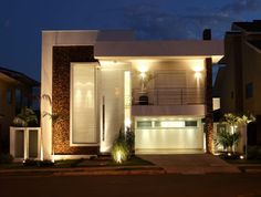 Fachada da casa com porta pivotante laqueada na cor branca, composta com elementos em pedras para a composição da mesma.