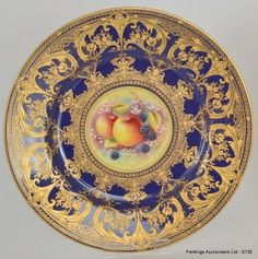 A 20th Century Royal Worcester cabinet plate decorated with a central handpainted roundel by T. Nutt of fruit and berries against a mossy ground, with royal blue border and overlay radiating gilt foliate scroll decoration, gold printed mark, diameter 27cm,
