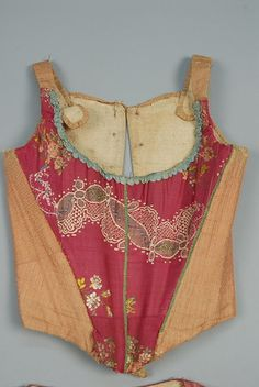 BODICE and CORSET ENSEMBLE, EUROPEAN, LATE 18th - EARLY 19th C.  Cranberry silk faille with polychrome floral brocade, the square-neck bodice having folded front collar, narrow double breast and short sleeve with pleated and pointed cuff, peplum back. Corset front pieced with cranberry brocade and a tan dotted sawtooth stripe, the back in a similar dotted stripe. Both pieces trimmed in aqua ribbon and lined in linen
