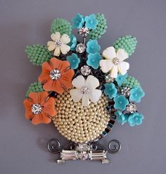 "basket brooch, seed pearl body, orange and aqua molded glass flowers, mother-of-pearl flowers, clear rhinestones, 4"" by 3""."
