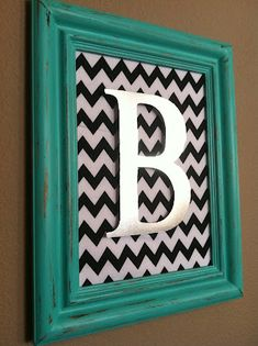 Fabric or scrapbook paper for a background with a painted initial in an open frame. love
