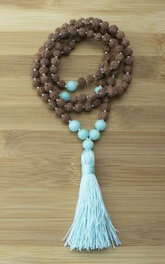 This high quality handcrafted full length meditation mala beads necklace features rudraksha with bronzite guru and markers, brass accents and a 100% cotton multi-colored tassel. Rudraksha, actually a