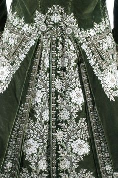 Detail back view, 3-piece court coat, France, c. 1790. Green velvet, heavily embellished with floss silk flowerheads and foliage; waistcoat: ivory silk satin with floral embroidery; black satin breeches.