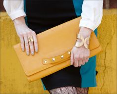 Grab hold of a mustard, oversized clutch for fall embellished with some spikes! #fallcolor #tjmaxx