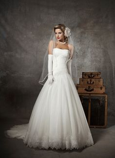 Justin Alexander wedding dresses style 8625 Strapless soft sweetheart pleated french tulle accented with chantilly lace, asymmetrical drop waist, tulle skirt with chantilly hem lace, buttons over back zipper, chapel length train.