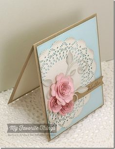 -a Kraft Card Stock card base. -cut High Tea Party Doily Die-namics and sponged the edges. -trimmed off the side and adhered it to a layer of Sno Cone Cardstock- popped them both on the base on foam tape-cut Leaf-Filled Flourish Die-namics -sponged the edges, and adhered it to my doily-made some flowers using Mini Hybrid Heirloom Rose Die-namics and Mini Royal Roses Die-namics and adhered them-sentiment was stamped on a Sentiment Strips Die-namics and the end slipped under the flowers