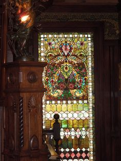 Stunning and colourful stained glass window and wooden details in Victorian interior.
