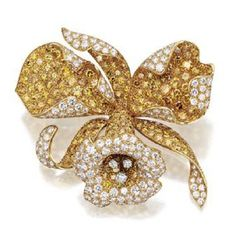 FANCY COLORED DIAMOND AND DIAMOND FLOWER BROOCH, VAN CLEEF & ARPELS. Designed as an orchid, pavé-set with 215 round diamonds of yellow hue weighing approximately 13.75 carats and with 170 round near colorless diamonds weighing approximately 9.00 carats, mounted in 18 karat gold, signed Van Cleef & Arpels, numbered 19144.