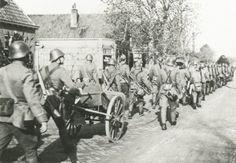 Militairen van het 16e Regiment Infanterie op mars naar de stellingen, onder medevoering van onder meer een mitrailleurkar.