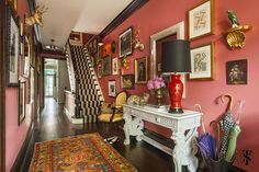 Eclectic foyer with coral walls, gallery wall art, & striped stair runner by Summer Thornton Design, Inc. Interior Design Process, Interior Design Advice, Luxury Interior Design, Interior Design Kitchen, Interior Design Inspiration, Design Projects, Coral Walls, Naples Florida, Lincoln