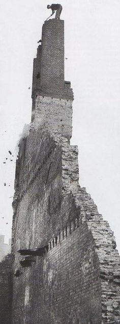 This is the photo that would trigger vertigo in most people! A workman perched atop this shaky chimney, all that is left of the building, is chipping away with a hammer. London during the Blitz, 1940. The question is: how did he climb up there?