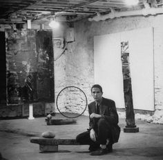 Artist Robert Rauschenberg sitting on one of his sculptures in his studio, among his other paintings and sculptures (1953)