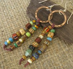 Many colors and shapes of tiny glass beads are strung on waxed linen and dangle from textured copper hoops on sterling silver handmade ear wires.