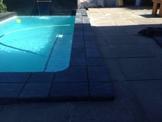 Pool coping re-tiled with black slate tiles and black grout