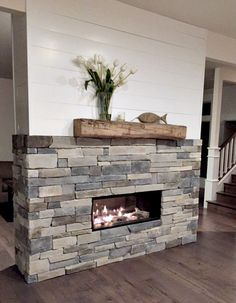 Double Sided Fireplace - designed my own. Antique oak beam, shiplap, mixed rock and Valor two-sided Linear Fireplace (Long Beach Driftwood/rock option).Opposite side is same format w/Flat screen TV mounted. Also hid the cable Boxes & DVD player in a cubby on left side using a tension push door - you can't even see it!