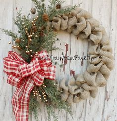 Red/Gold Plaid Christmas Burlap Wreath accented with faux pine greenery, pinecones, gold balls and completed with a beautiful red/gold plaid bow! This wreath works for Christmas and through the winter months! The perfect addition to your home...also makes a great gift! Wreaths measure between 20 to 22