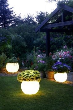 Buy your favorite flower pot and spray Rustoleum Glow-In-The-Dark paint.  Paint absorbs sunlight & glows at night.