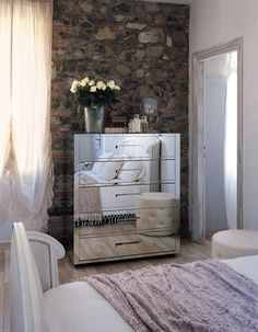mirrored dresser drawers against a stone or brick wall